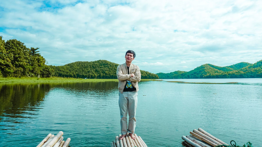 Portrait of man standing wooden raft at lake against sky