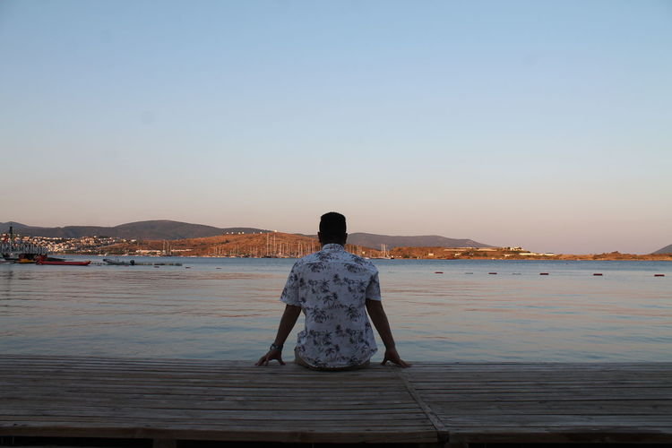 Rear view of man looking at sea while sitting on pier against clear sky
