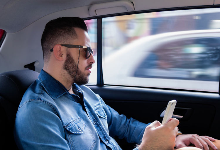 Man using mobile phone while sitting in car