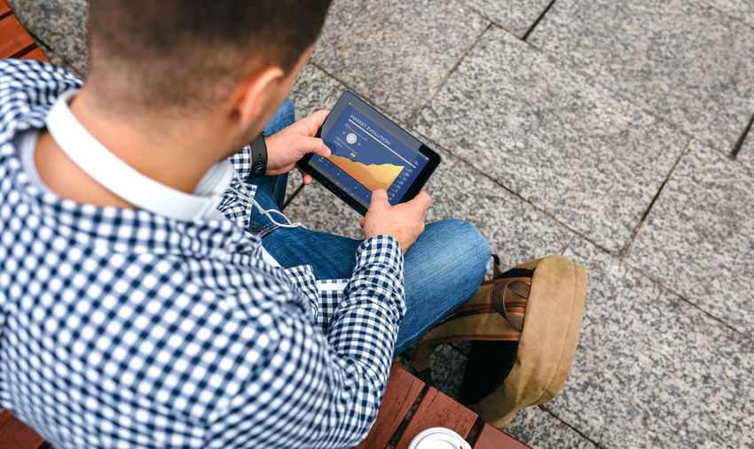 High angle view of man using digital tablet while sitting on bench