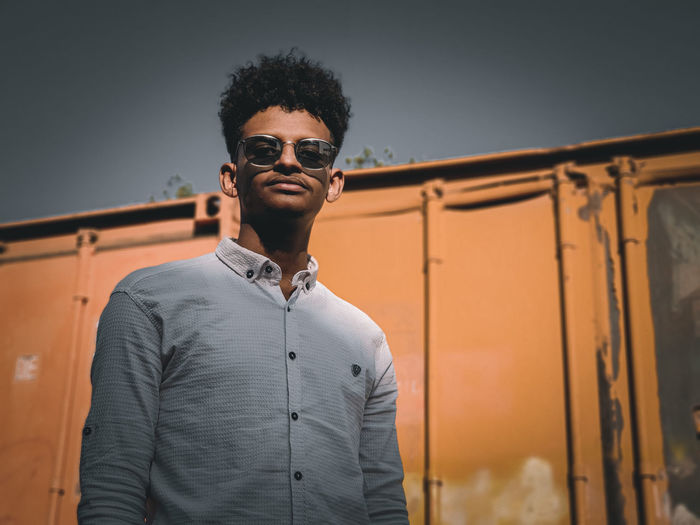 Portrait of young man wearing sunglasses while standing against sky