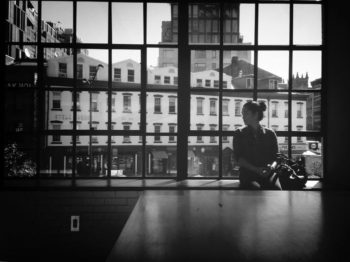 Front view of young woman looking away while sitting on window sill