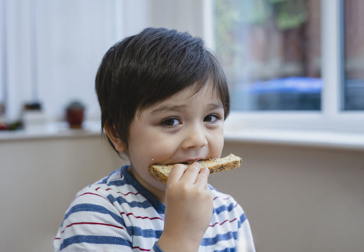 Portrait of cute boy eating food at home