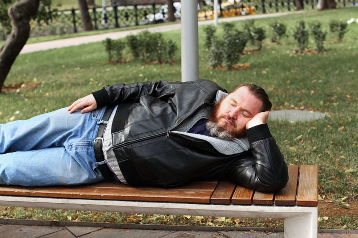 Lying Down Sleeping Relaxation Men Eyes Closed  Casual Clothing One Person Real People Lying On Back Day Resting Leisure Activity Lifestyles Young Adult Park Park - Man Made Space Seat Plant Contemplation Napping Jeans Hairstyle