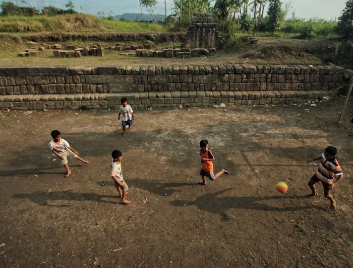 Children play football near the location of Plaosan Temple in Klaten, Central Java, Indonesia. The field that are same location of cultural heritage areas of Prambanan Temple made the field must be stop from any of activities. Sport Men Playing Togetherness Sports Team Soccer Competitive Sport Football Soccer Player Children Soccer Field Soccer Ball Sportsman Game Kids' Soccer Goalie Soccer Team