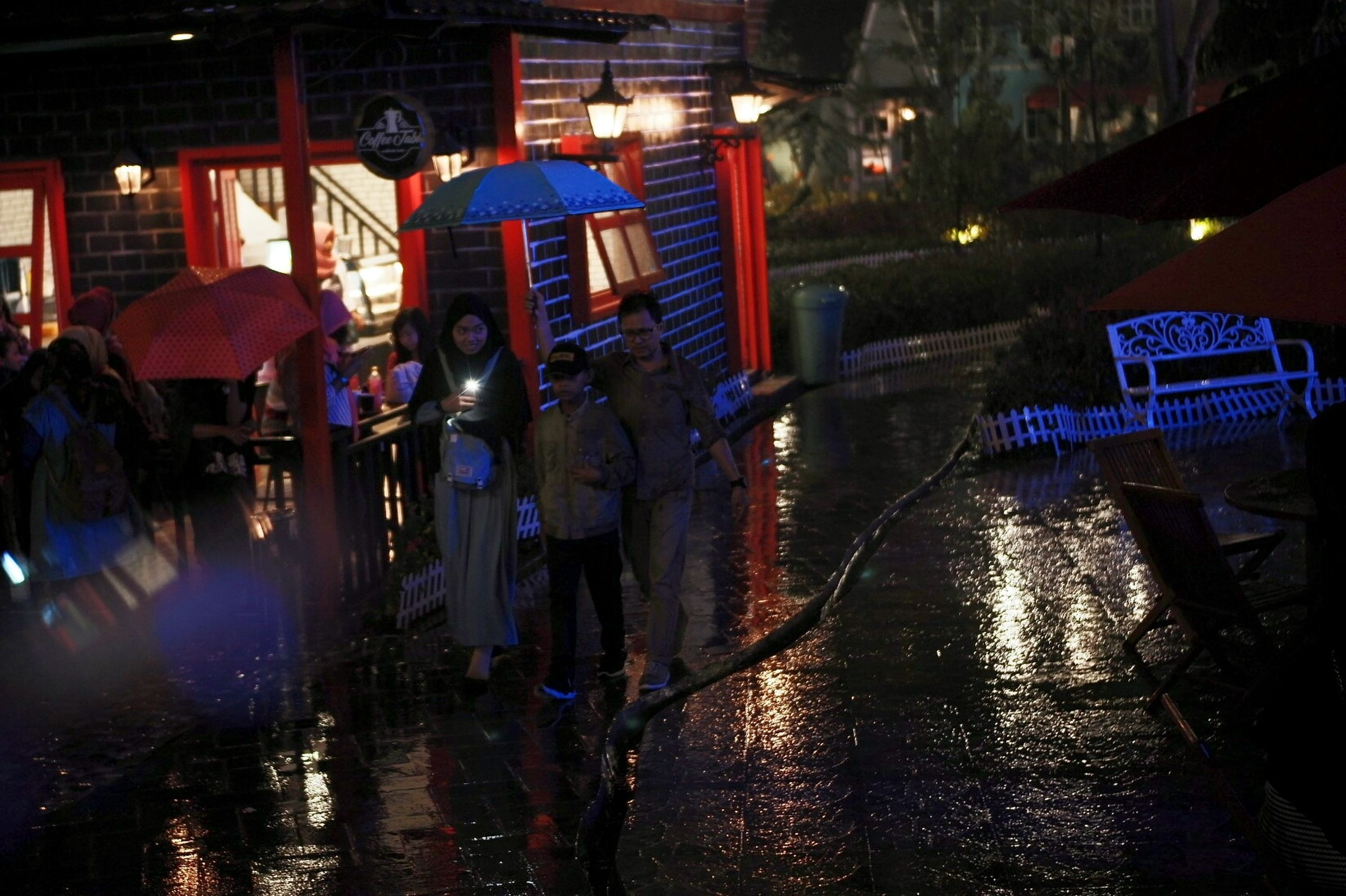 water, night, group of people, city, architecture, illuminated, wet, real people, men, protection, umbrella, built structure, transportation, people, rain, street, standing, building exterior, outdoors, rainy season, canal