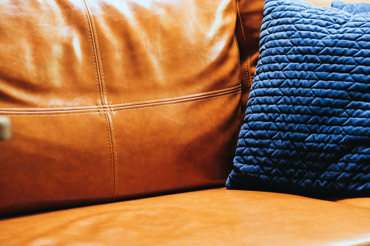 Close up detail of blue pillow on leather sofa Decor Leather Living Orange Pillow Art And Craft Blue Brown Business Close-up Clothing Cushion Decoration Decorations Decorative Fashion Flooring Full Frame Furniture Furniture Details Home Interior Indoors  Interior Design Jeans Leather Leather Sofa Living Room Luxury No People Orange Color Pattern Pillow Selective Focus Sofa Still Life Textile Wood - Material