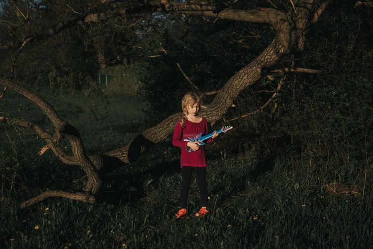 Full length of girl standing on tree