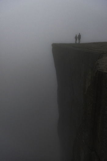 People standing on cliff against sky