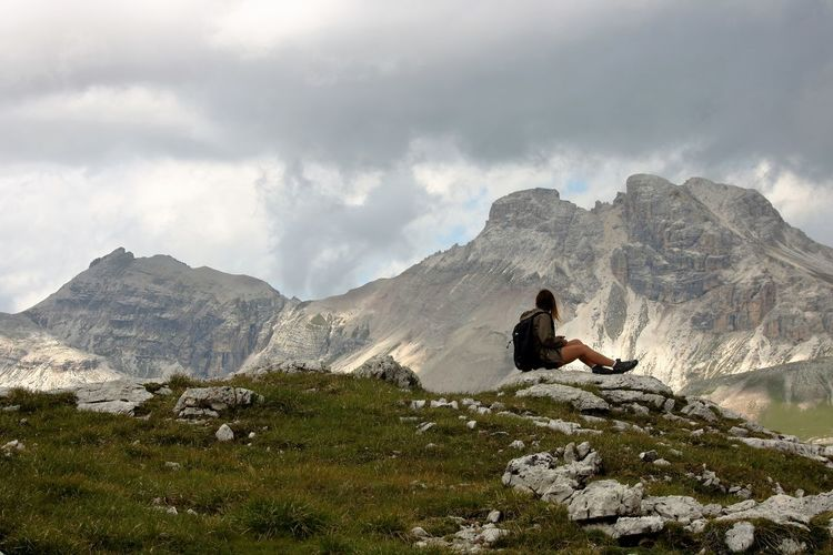 Woman Sitting On Rock Against Mountains
