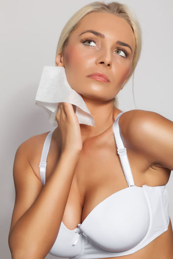 Young woman cleaning neck with tissue paper against white background
