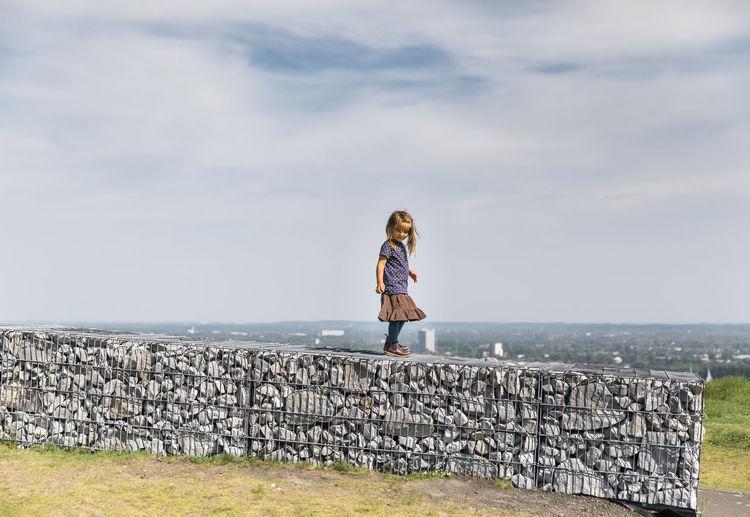 Full length of girl standing on stone wall against sky