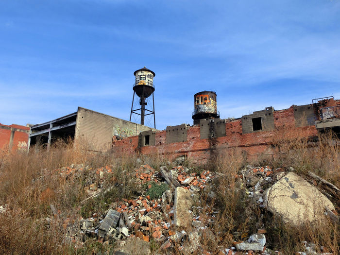 Low angle view of abandoned buildings against blue sky