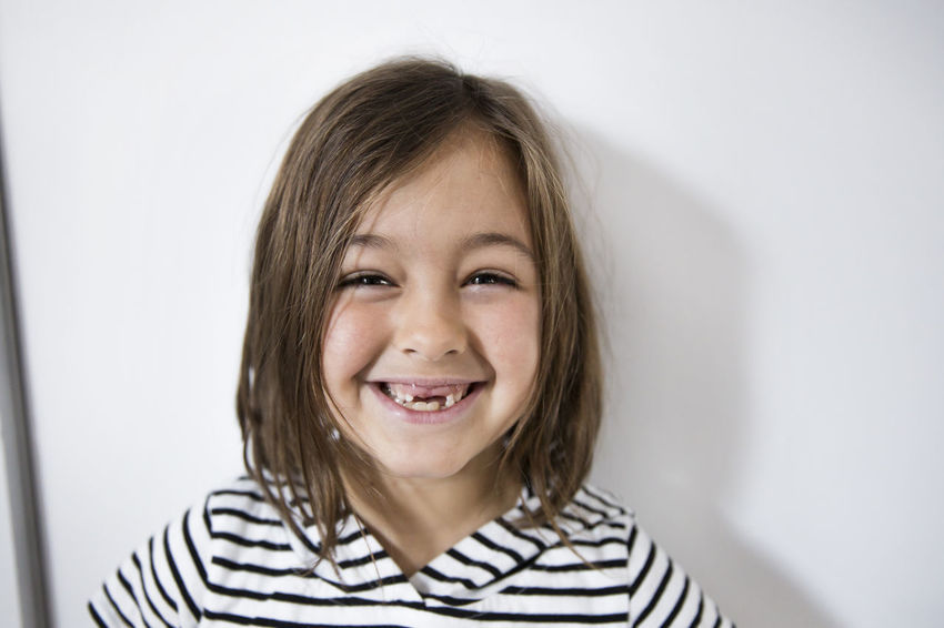 Head Shot  Blond Hair Casual Clothing Cheerful Child Childhood Children Only Close-up Day Front View Girl Girls Happiness Headshot Indoors  Looking At Camera Missing Teeth Missing Tooth One Girl Only One Person People Portrait Smiling Striped Toothy Smile