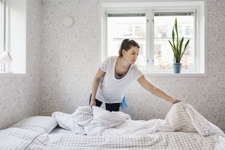 Full length of woman standing on bed at home