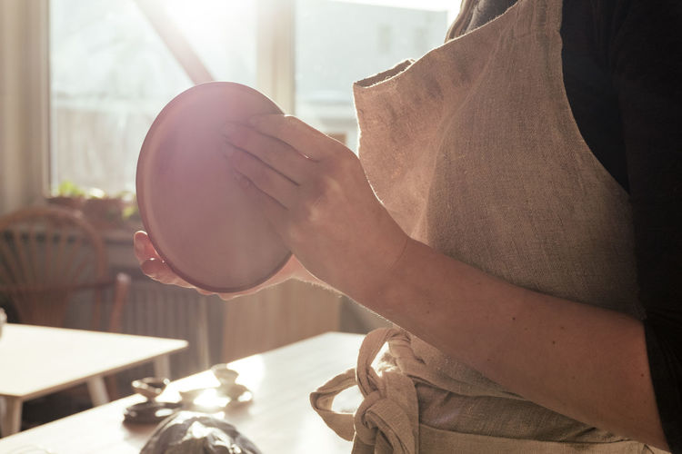 Midsection Of Woman Holding Plate In Kitchen At Home