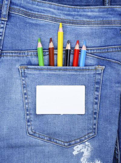 Directly above shot of colored pencils in jeans pocket
