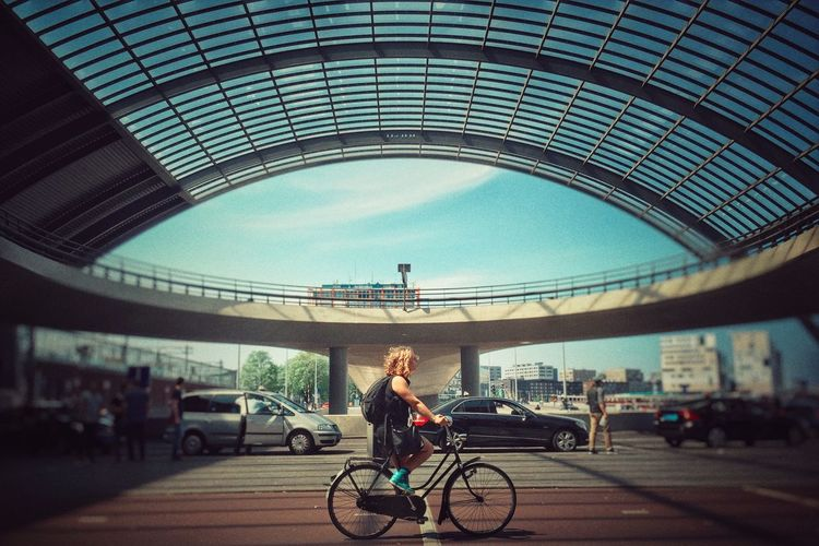 Side view full length of woman riding bicycle at amsterdam centraal railway station