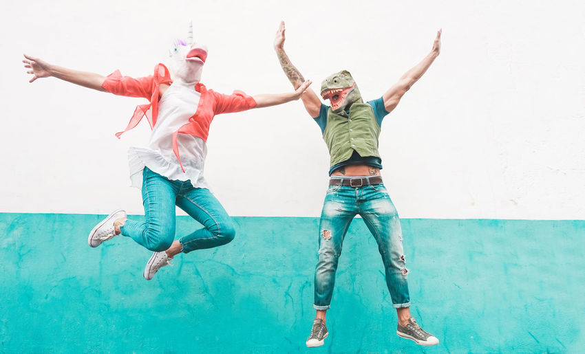 Friends Wearing Masks While Jumping Against Wall