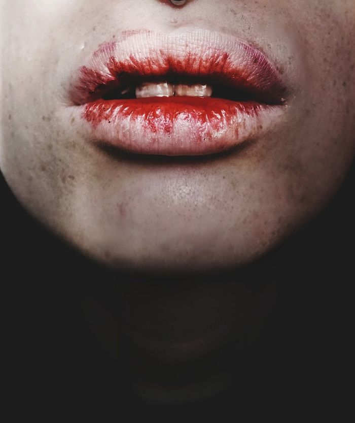 Close-up of woman lips against black background