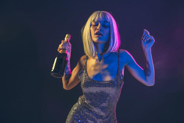 Woman holding bottle against black background
