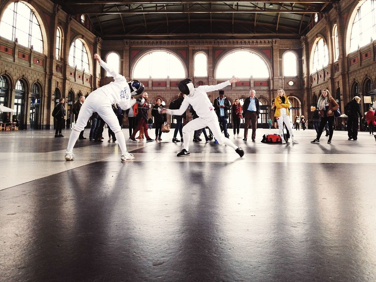 Action shot of two people fencing with witnessing spectators