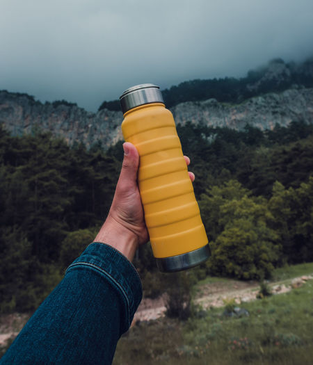Male hand holding a steel yellow thermo bottle on nature background.