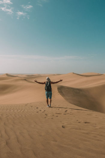 Man with arms outstretched walking on desert against sky