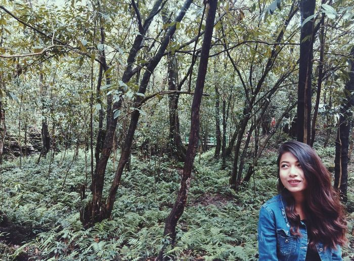 Smiling Young Woman Standing Against Trees At Forest