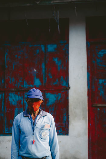 Man wearing hat standing against brick wall