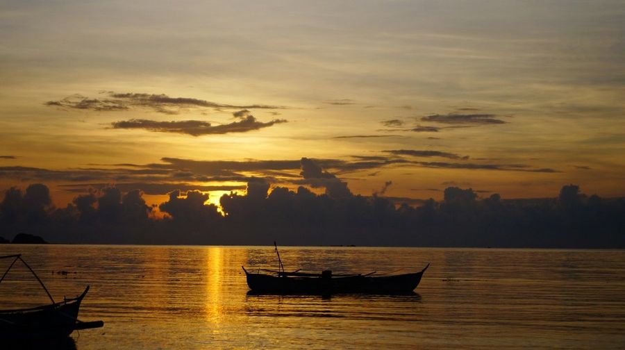 Silhouette boats in calm sea at sunset