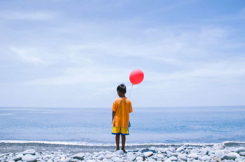 Rear view of boy with red helium balloon standing on shore at beach against sky