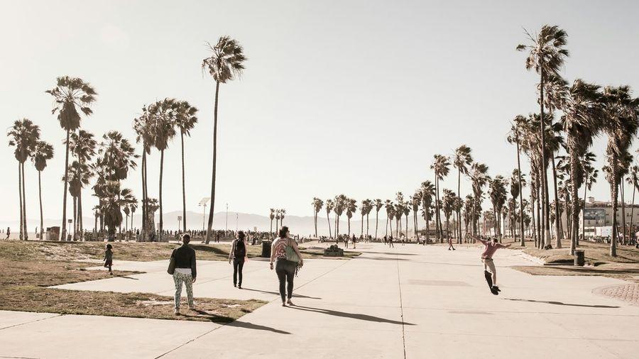 People walking on pedestrian walkway against clear sky