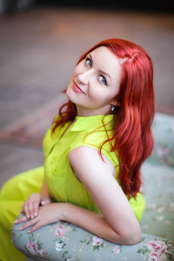 Portrait Of Smiling Beautiful Woman With Redhead Sitting On Seat