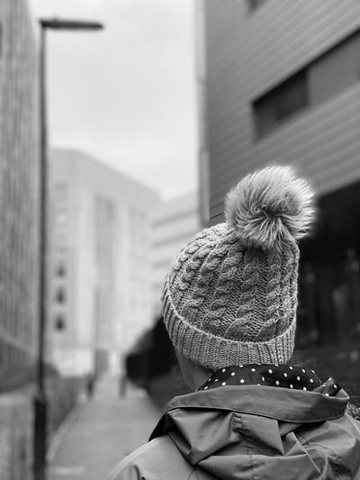 Rear view of woman walking in city during winter