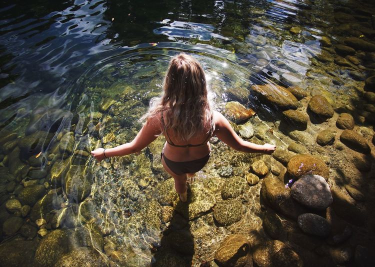 Rear view of young woman swimming in water