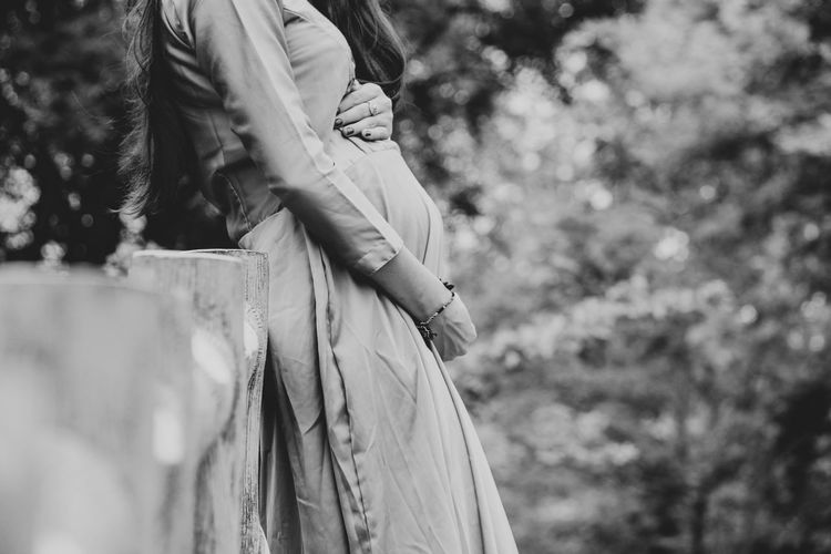 Midsection of pregnant woman with hands on stomach standing outdoors