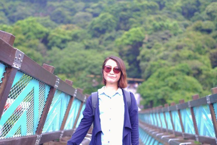 Woman standing against trees on footbridge