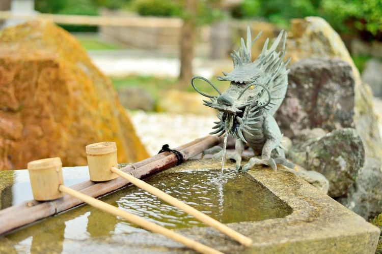 Japanese washbasin, tsukubai, with a dragon fountain and bamboo ladle. Bamboo - Material Close-up Day Dragon Dragon Sculpture Dragon Statue Drinking Fountain Focus On Foreground Fountain Japan Japan Photography Japanese  Japanese Architecture Japanese Culture Japanese Style Ladle Nature No People One Animal Outdoors Tsukubai Washbasin Water