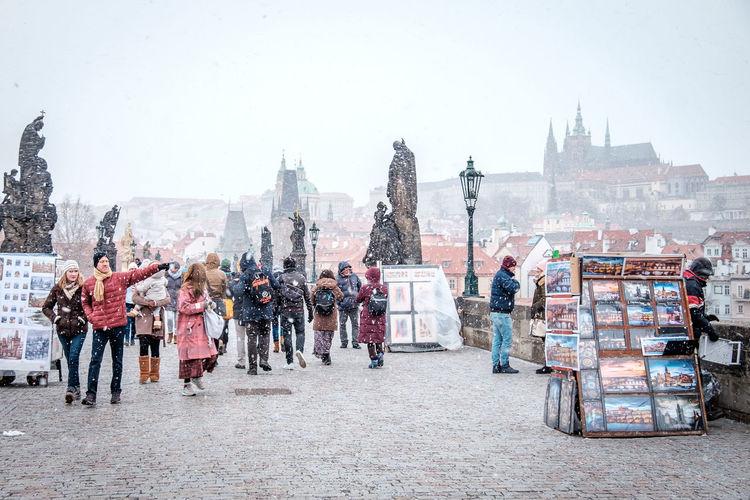 People walking on street in city against sky during winter