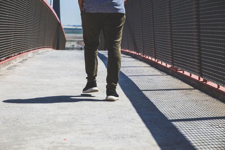 Low section of man walking on bridge