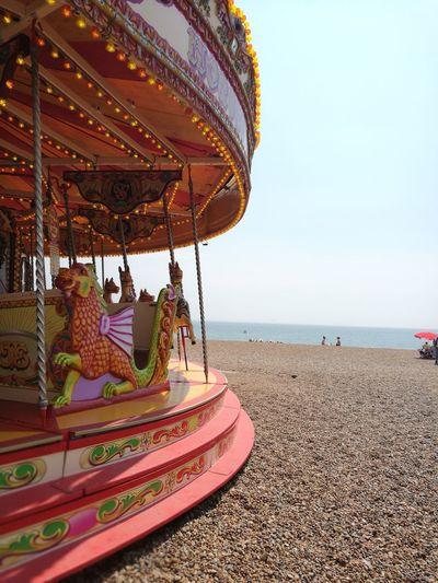 Merry-go-round at beach against clear sky