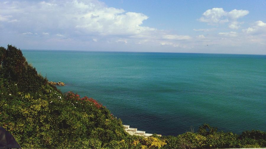 Scenic view of sea by hill against cloudy sky