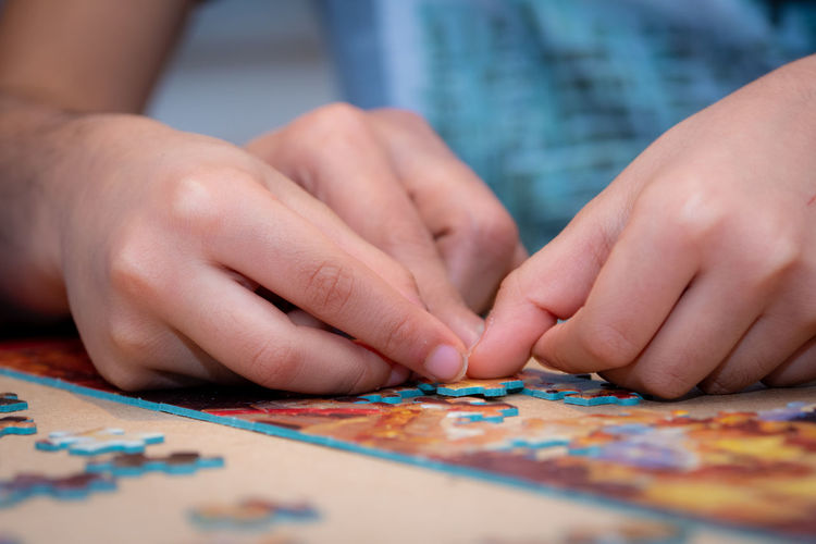Cropped hands of people playing jigsaw puzzle