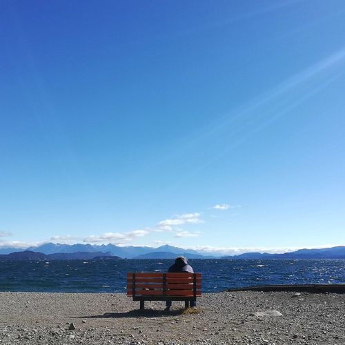 Rear view of woman sitting on bench by lake against blue sky during sunny day