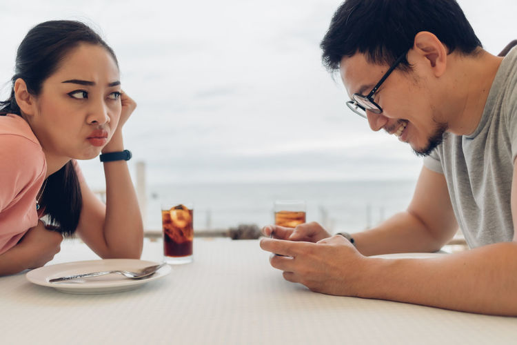 Young couple sitting on table at shore