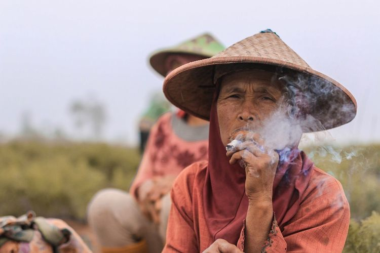 Senior Woman Smoking Marijuana Joint At Farm