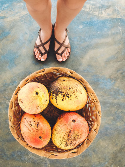 Low section of woman standing on mangoes in wicker basket at beach
