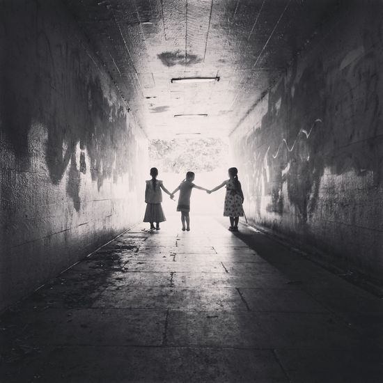 Rear View Of Siblings Holding Hands In Tunnel