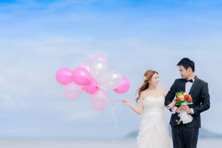 Bride and groom standing against sky